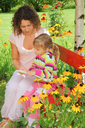 young woman reads the book to little girl in garden photo