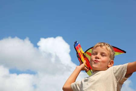 boy plays kite against sky  photo