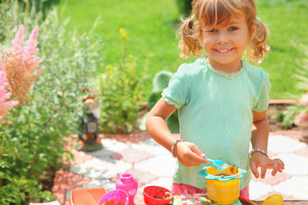 Smiling little girl plays cook in garden  photo