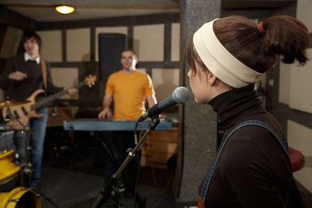 electro: S�nger M�dchen in der N�he von Mikrofon. Leiter der Mikrofon im Mittelpunkt. Elektro-Gitarrist und Keyboarder in unscharf Lizenzfreie Bilder
