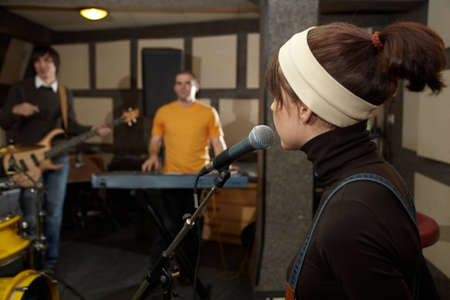 vocalist girl near microphone. focus on head of microphone. electro guitar player and keyboarder in out of focus photo