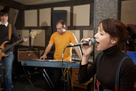 micro recording: vocalist girl is singing. electro guitar player and keyboarder in out of focus