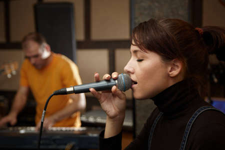 a rehearsal: vocalist girl is singing in studio. keyboard player in out of focus Stock Photo