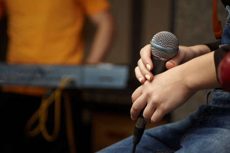 vocalist: microphone in hand of vocalist girl. keyboard player in out of focus