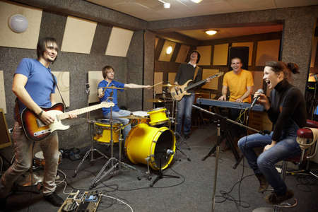 micro recording: a rock band working in studio. the joy of creation