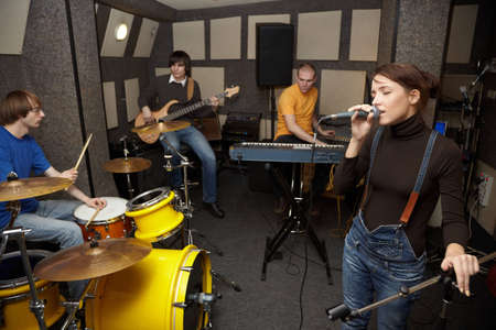 micro recording: a rock band working in studio. vocalist girl is singing. focus on clothers of vocalist girl Stock Photo