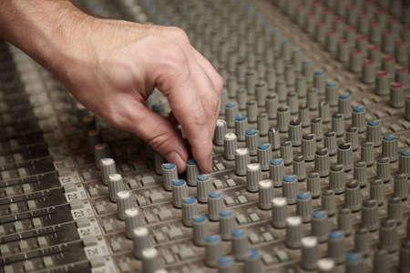 pult: suono produttore ruotando un regolatore di vecchio mixer audio sporco pult