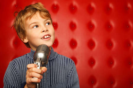 Portrait of boy with microphone on rack against red wall looking aside. Horizontal format. photo