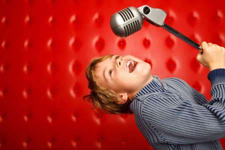 child singing: Singing boy with microphone on rack against red wall. Horizontal format. Stock Photo