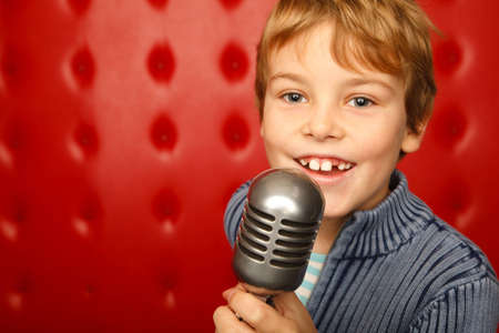 performer: Singing boy with microphone on rack against red wall. Close up. Horizontal format. Stock Photo