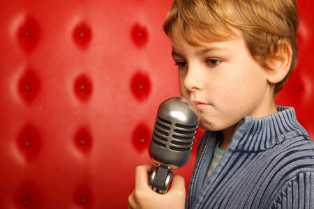 Sad boy with microphone on rack against red wall. Close up. Horizontal format. photo