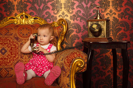 Little girl in red dress talking vintage phone. Interior in retro style. Horizontal format. photo