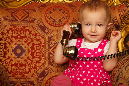 Little girl in red dress talking vintage phone. Interior in retro style. Horizontal format. Close up. photo