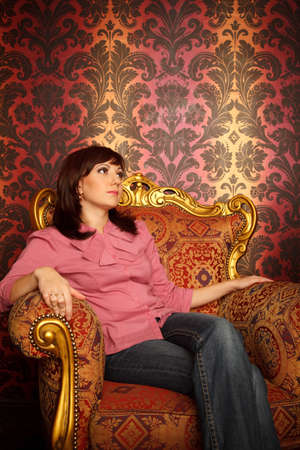 Portrait of girl sitting in armchair. Interior in retro style. Looking aside. Vertical format. Stock Photo - 9113472