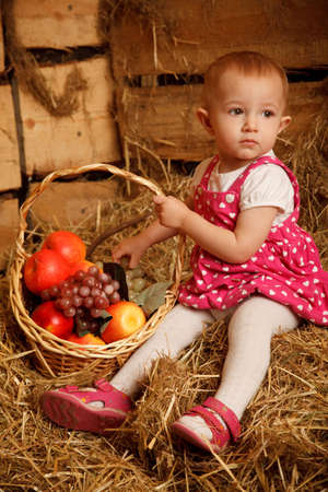 The little girl on straw with a basket of fruit against the wall of boards. Vertical format. photo