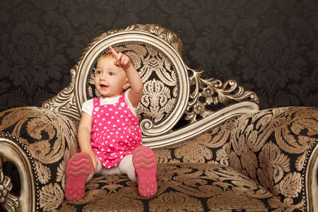 Little girl in red dress sitting on retro armchair with finger pointing up. photo