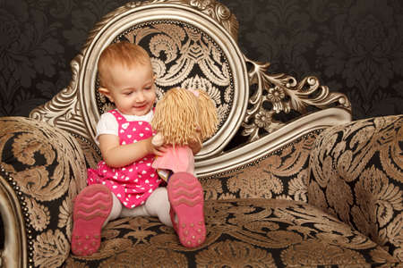 Little girl in red dress sitting on retro armchair with doll in hands. Horizontal format. Stock Photo - 9113404