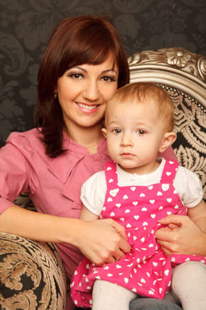 Mother and daughter on her lap sitting in armchair. Interior in retro style. Stock Photo - 9113222