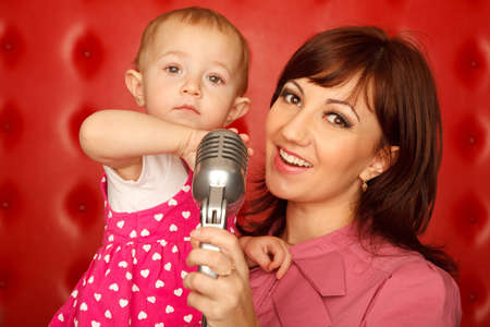 Portrait of mother and doughter with microphone on rack against red wall. Horizontal format. photo