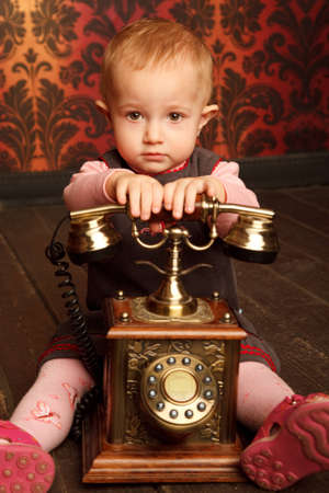 Portrait of little girl sitting with retro phone. Interior in retro style. Vertical format. photo