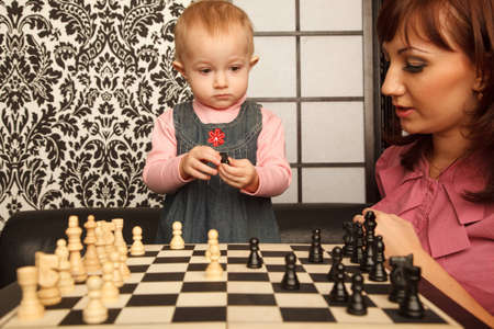 Mother and her little doughter near chess board. Horizontal format. Indoor. photo