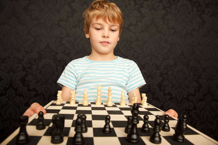 Portrait of boy in T-shirt with chessboard against the wall with ornament.  Horizontal format. photo