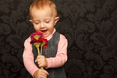 Portrait of little girl with flowers in her hands against ornamental wall. photo