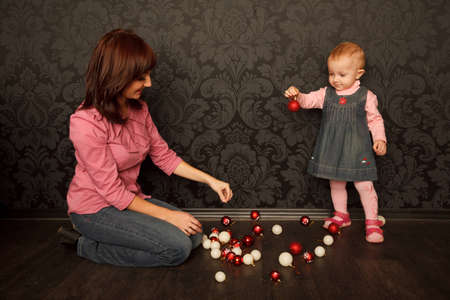 Mother and daughter consider Christmas decorations. Red and white balls. photo