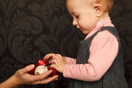 Little girl takes Christmas toys from the hands of mothers. Close up. Horizontal format. Stock Photo - 9112579