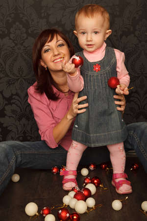Little girl and her mother are playing with Christmas toys on floor. Vertical format. Stock Photo - 9113291