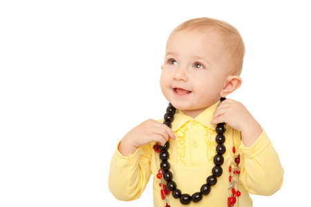 Portrait of little girl in yellow shirt with beads on white background. photo