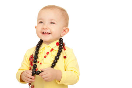Portrait of smiling little girl in yellow shirt with beads on white background. photo