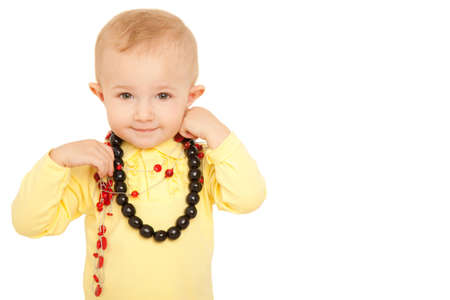 Portrait of smiling little girl looks into camera in yellow shirt with beads on white background. photo