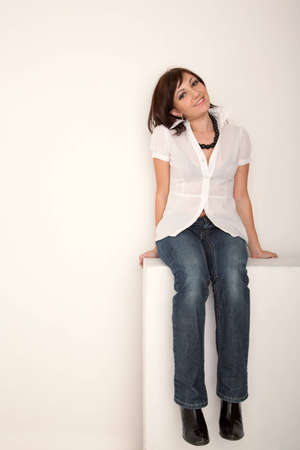 Smiling girl in jeans and white shirt sitting in white studio. Vertical format. photo