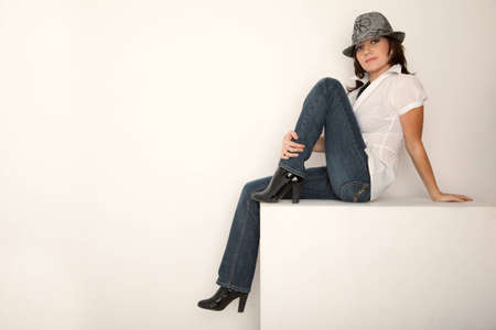 Girl in jeans, hat and white shirt sitting in white studio. Horizontal format. photo