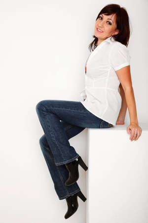 Portrait of girl in jeans and white shirt sitting in white studio. Vertical format. photo