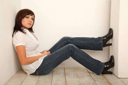 Portrait of pensive girl in jeans and white shirt sitting in white studio. photo