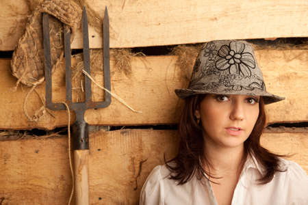 hayloft: Portrait of girl in hat in hayloft with pitchfork and bast shoes. Horizontal format. Stock Photo