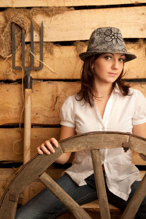 Portrait of girl in hat in hayloft with pitchfork and bast shoes. Vertical format. photo