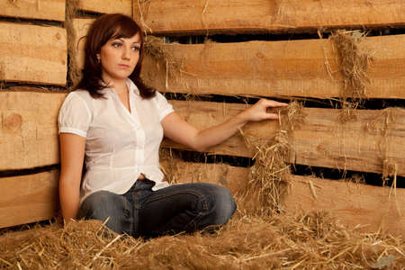 Portrait of girl in white shirt and blue jeans sitting on pile of straw in hayloft. photo