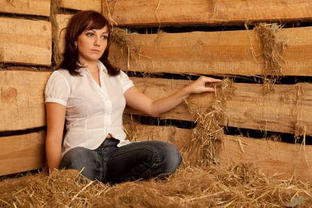 hayloft: Retrato de joven en camisa blanca y pantalones vaqueros, sentado sobre una pila de paja en el pajar. Foto de archivo