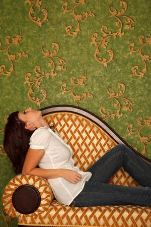 Girl in jeans sits on sofa and looks at wall with patten wall-paper Stock Photo - 9113554
