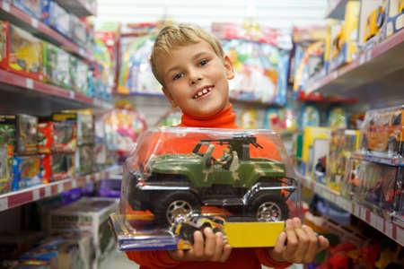 toy shop: Il ragazzo in negozio con la macchina giocattolo nelle mani