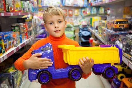 toy shop: Il ragazzo nel negozio con camion giocattolo nelle mani