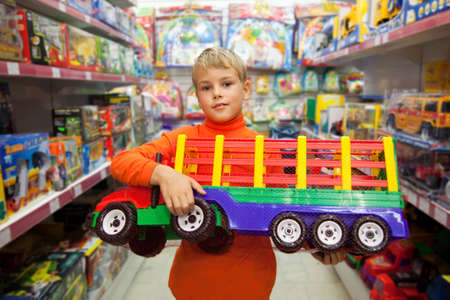 The boy in shop with the big model of the truck in hands Stock Photo - 9110499
