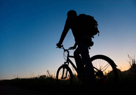 Silhouette of the bicyclist against the dark sky photo