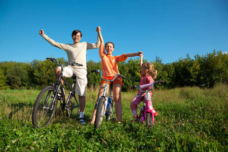 joyfully: Parents with the daughter on bicycles in park a sunny day. Have joyfully thrown up hands.