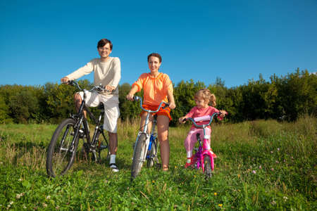 Parents with the daughter on bicycles in park a sunny day. Keep for hands. photo