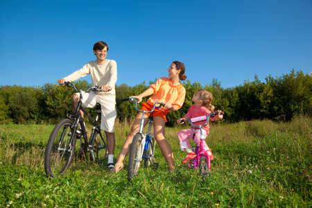 Family from three persons on bicycles in the country. Mum with a daughter look at the daddy. photo