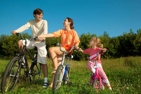 The father, mum and daughter on bicycles in park. To keep the friend for the friend hands. photo